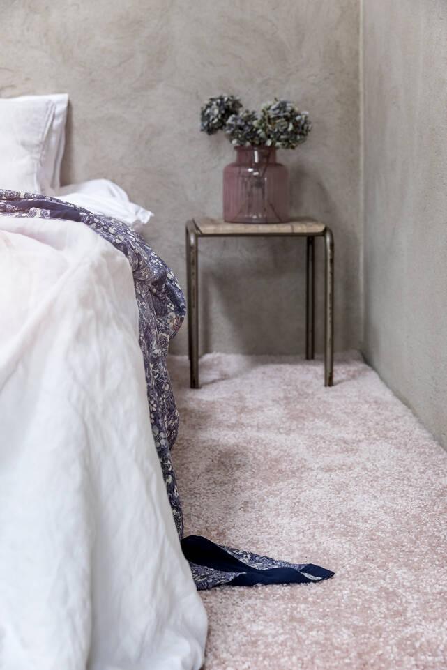 Roze, langwerpig shaggy piramit 3.5 kg - vloerkleed in een slaapkamer.