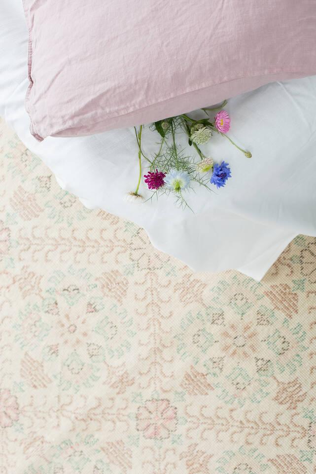 Wit,  colored vintage - turkiet - vloerkleed in een slaapkamer.