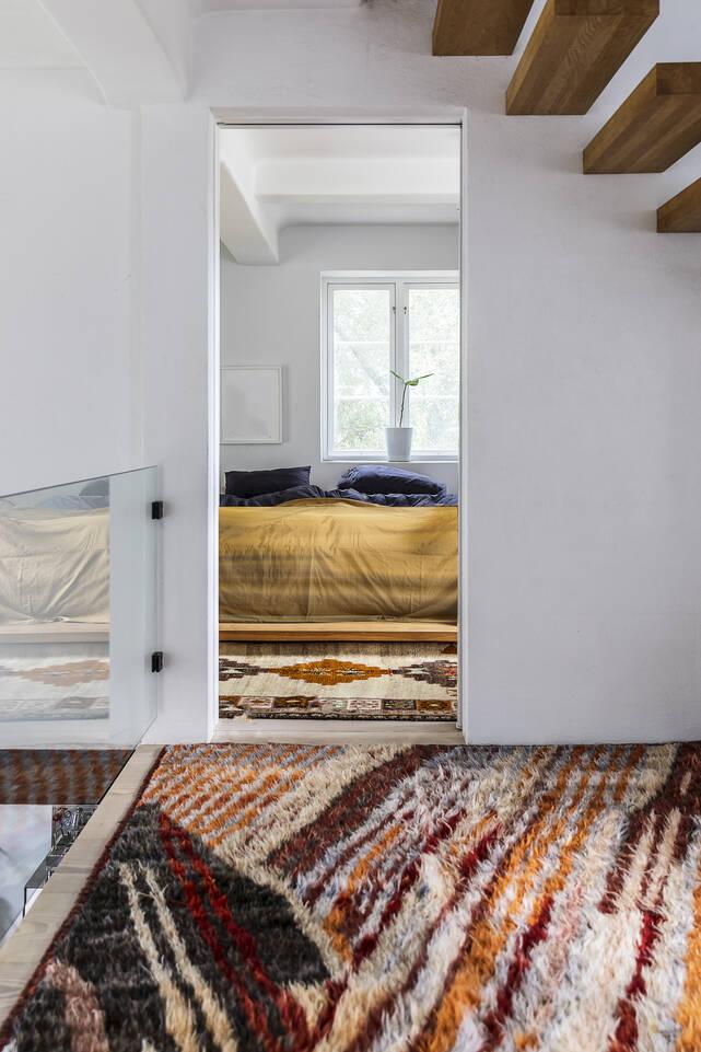 Bruin / gele, langwerpig moroccan berber - afghanistan - vloerkleed in een slaapkamer.